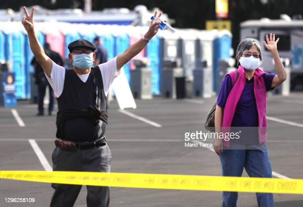 People react after receiving the COVID-19 vaccine at a mass vaccination site in a parking lot for Disneyland Resort on January 13, 2021 in Anaheim,...