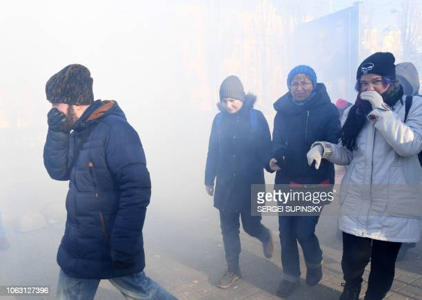 People react after the activists of far-right groups attack with smoke bomb participants of the march of transgender people in Kiev on November 18,...