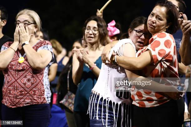 People react and embrace each other during an interfaith vigil for victims of a mass shooting which left at least 20 people dead on August 4 2019 in...