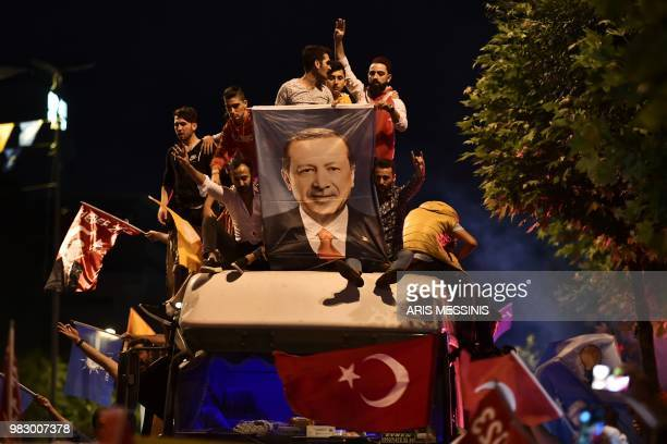 TOPSHOT People react and wave flags outside the Justice and Development Party headquarters in Istanbul on June 24 during the Turkish presidential and...