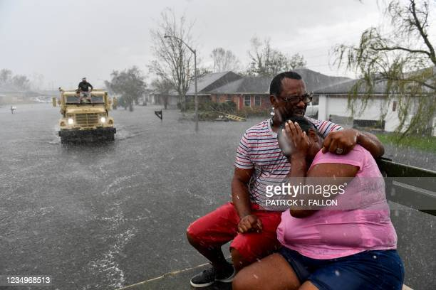 People react as a sudden rain shower soaks them with water while riding out of a flooded neighborhood in a volunteer high water truck assisting...