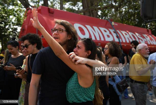 TOPSHOT People react as firefighters inspect Rio de Janeiro's treasured National Museum one of Brazil's oldest on September 3 2018 a day after a...