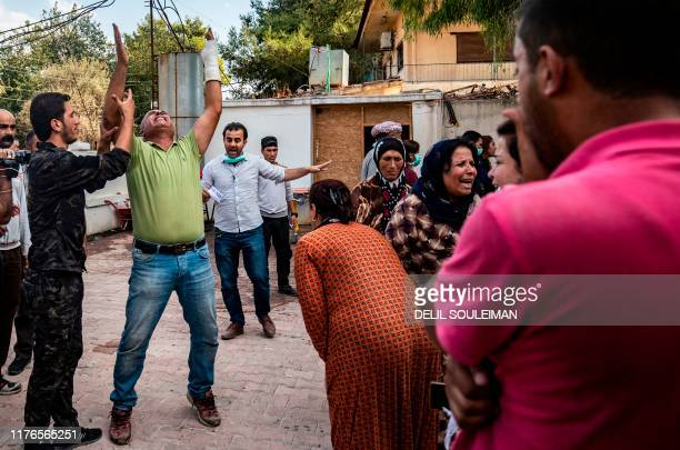 TOPSHOT People react as the body of a man killed during Turkish shelling in the area surrounding the Syrian Kurdish town of Ras alAin arrives at a...