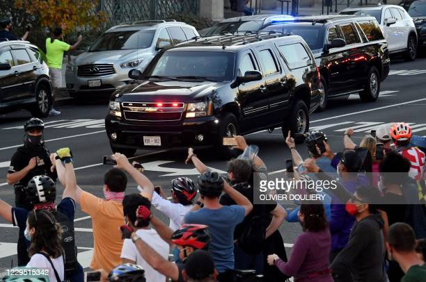 People react as the motorcade carrying US President Donald Trump returns to the White House on November 7, 2020 in Washington, DC., after Joe Biden...