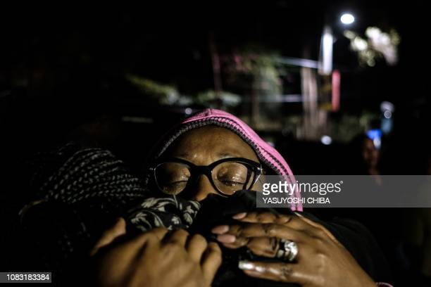 People react as they are reunited with family after being evacuated from the DusitD2 compound in Nairobi after a blast followed by a gun battle...