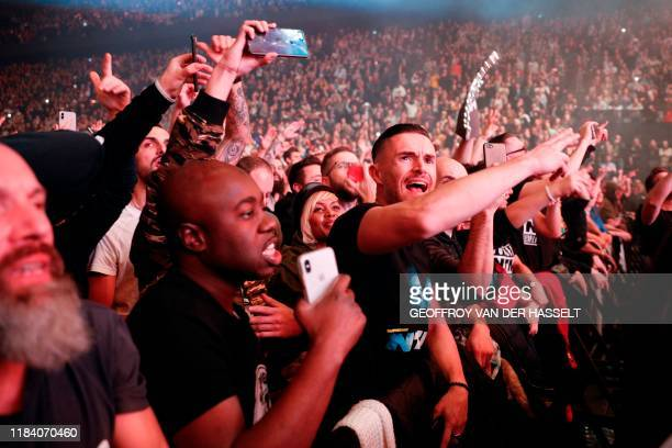 """People react as they attend a concert of French rap band """"Supreme NTM"""" at the AccorHotels Arena, in Paris on November 22, 2019."""