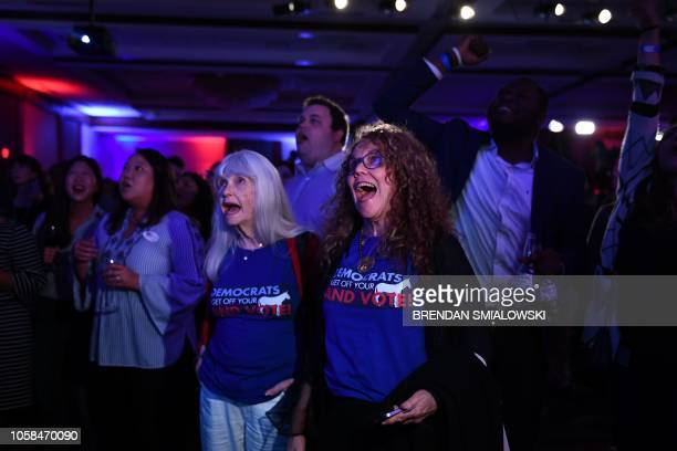 People react as they attend a midterm election night party hosted by the Democratic Congressional Campaign Committee November 6 2018 in Washington DC