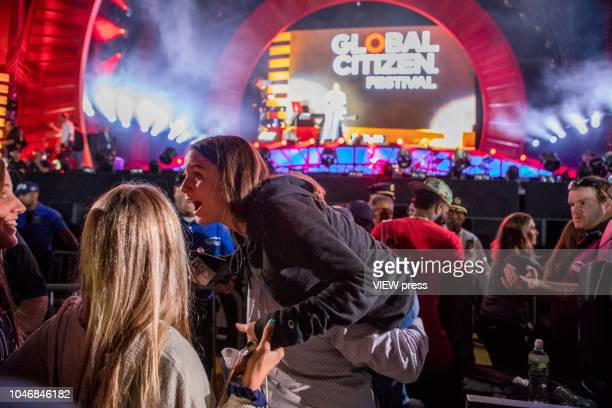 People react as they get cover after panic and confusion erupts at the Global Citizen Festival in Central Park on September 29 2018 in New York City...
