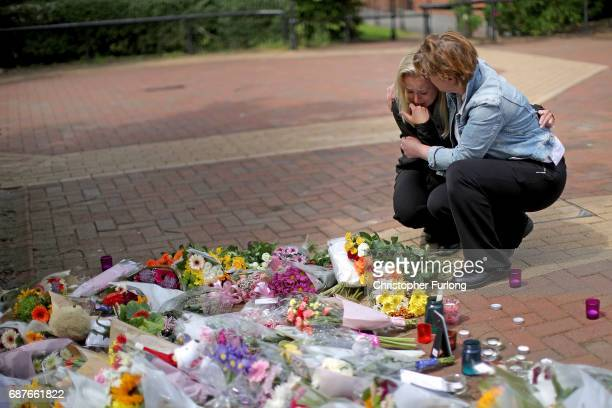People react as they lay lowers in the centre of the Lancashire village of Tarleton the home village of Georgina Callander and Saffie Rose Roussos...