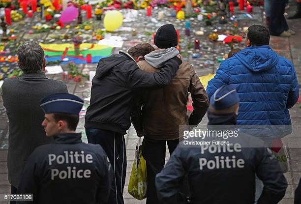 People react as they pay their respects at the Place De La Bourse in honour of the victims of yesterdays' terror attacks on March 23 2016 in Brussels...
