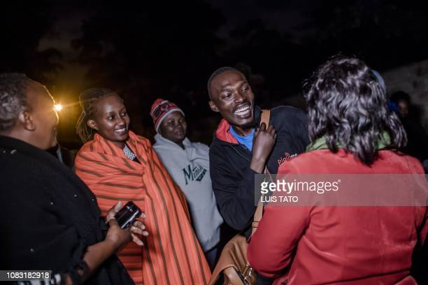 People react as they reunite after being evacuated from the DusitD2 compound in Nairobi after a blast followed by a gun battle rocked the upmarket...