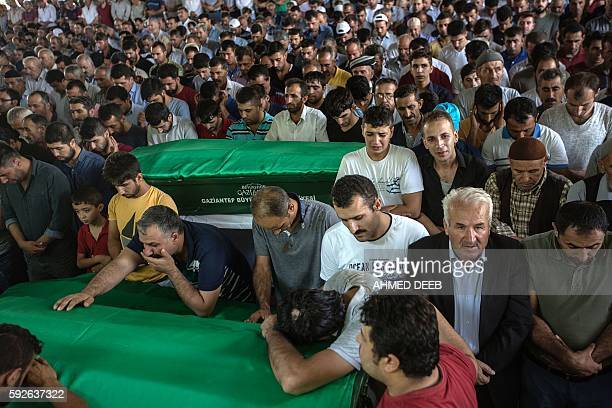 People react as they stand around coffins during a funeral for victims of last night's attack on a wedding party that left 50 dead in Gaziantep in...