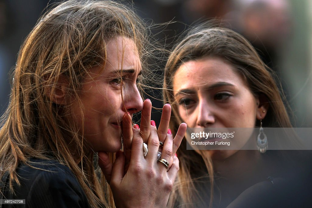 People react as they view tributes and flowers outside La Belle Equipe restaurant on Rue de Charonne following Fridays terrorist attack and France observes three days of national mourning on November 15, 2015 in Paris, France. As France observes three days of national mourning members of the public continue to pay tribute to the victims of Friday's deadly attacks. A special service for the families of the victims and survivors is to be held at Paris's Notre Dame Cathedral later on Sunday.