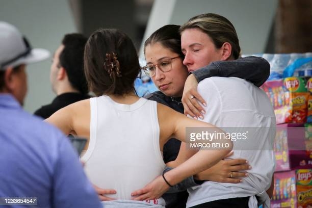 People react as they wait for news about relatives at the Community Center in Surfside, north of Miami Beach, Florida on June 25, 2021. - Four people...