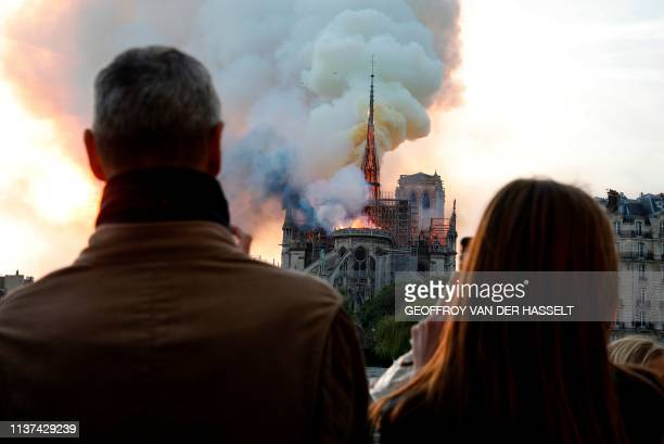 People react as they watch flames engulf the roof of the Notre-Dame de Paris Cathedral in the French capital Paris on April 15, 2019. - A colossal...