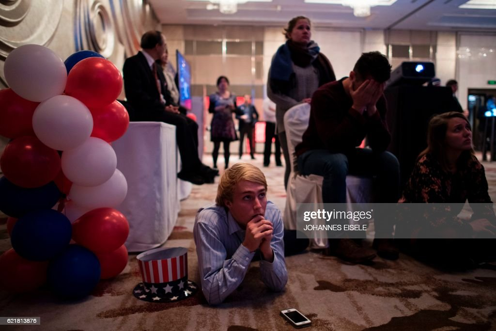 TOPSHOT - People react as they watch news on a screen to follow the results of the final day of the US presidential election at an event organised by the American consulate in Shanghai on November 9, 2016. US stock markets tumbled more than five percent in after-hours trading as Republican billionaire Donald Trump appeared poised to defeat Democratic rival Hillary Clinton in the race for the White House. /