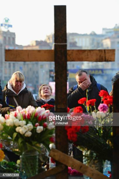 People react at a make shift shrine to the antigovernment demonstrators killed in yesterdays clashes with police in Independence square on February...