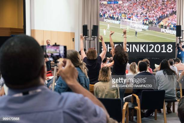People react at the media center in Helsinki as France scores a penalty during the Russia 2018 World Cup final football match between France and...