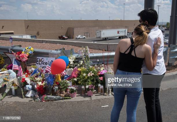 People react beside a makeshift memorial outside the Cielo Vista Mall WalMart where a shooting left 20 people dead in El Paso Texas on August 4 2019...