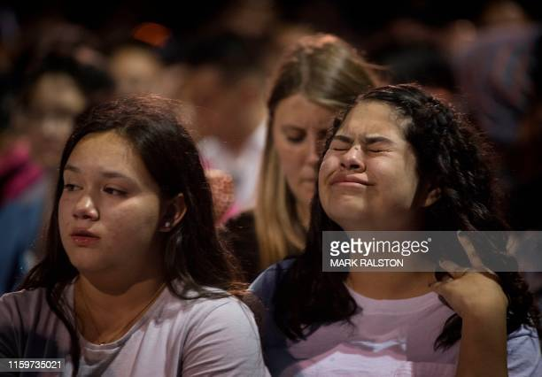 People react during a prayer and candle vigil organized by the city after a shooting left 20 people dead at the Cielo Vista Mall WalMart in El Paso...