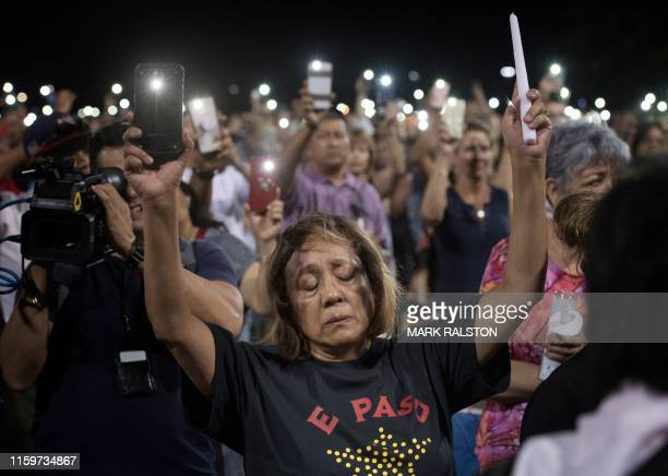 People react during a prayer vigil organized by the city after a shooting left 20 people dead at the Cielo Vista Mall WalMart in El Paso Texas on...