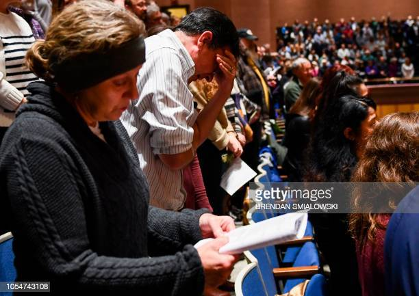 People react during a vigil to remember the victims of the shooting at the Tree of Life synagogue the day before at the Allegheny County Soldiers...
