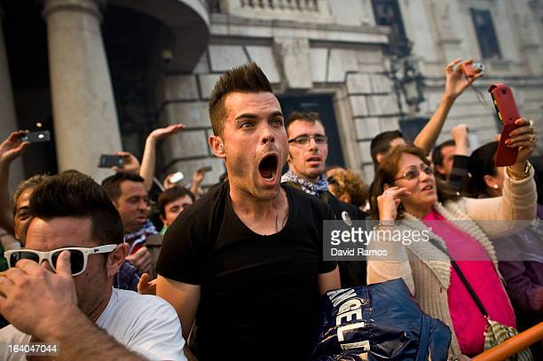 People react during the 19th 'Mascleta', an explosive barrage of firecrackers and fireworks celebrating the arrival of the Spring on March 19, 2013...