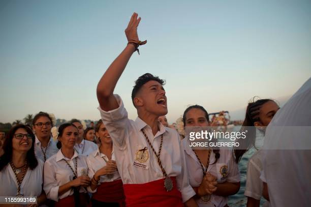 People react during the Virgen del Carmen brotherhood procession for celebrations marking Carmen Day in Malaga southern Spain on July 16 2019
