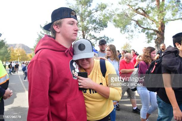 People react near Central Park after a shooting at Saugus High School in Santa Clarita, California on November 14, 2019. - At least four people were...