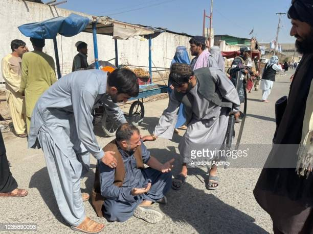 People react near the scene after a bomb blast hits Shia community mosque in Afghanistanâs southern Kandahar province on October 15, 2021