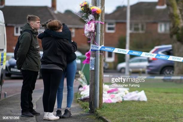People react next to floral tributes outside a home in Valley View Brownhills Walsall where Mylee Billingham aged eight was stabbed and later died in...