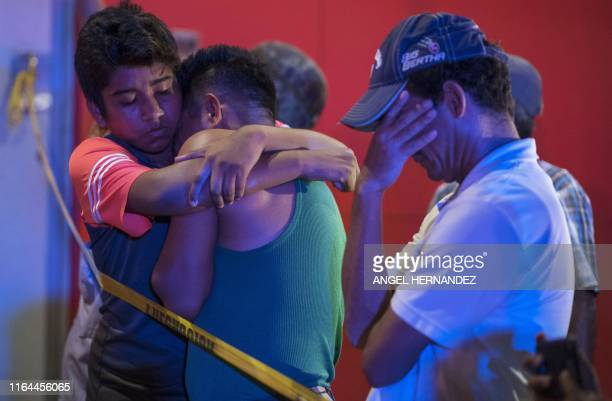 TOPSHOT People react outside a bar where 23 people were killed by a fire in Coatzacoalcos Veracruz on August 28 2019 At least 23 people were killed...
