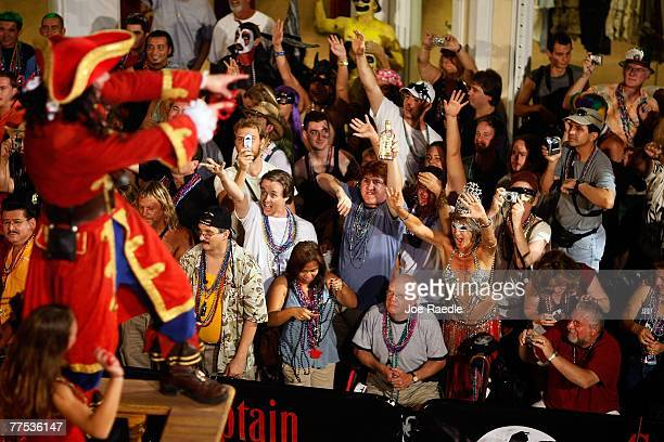 People react to a float passing through the streets as they participating in the Fantasy Fest Masquerade parade October 27 2007 in Key West Florida...