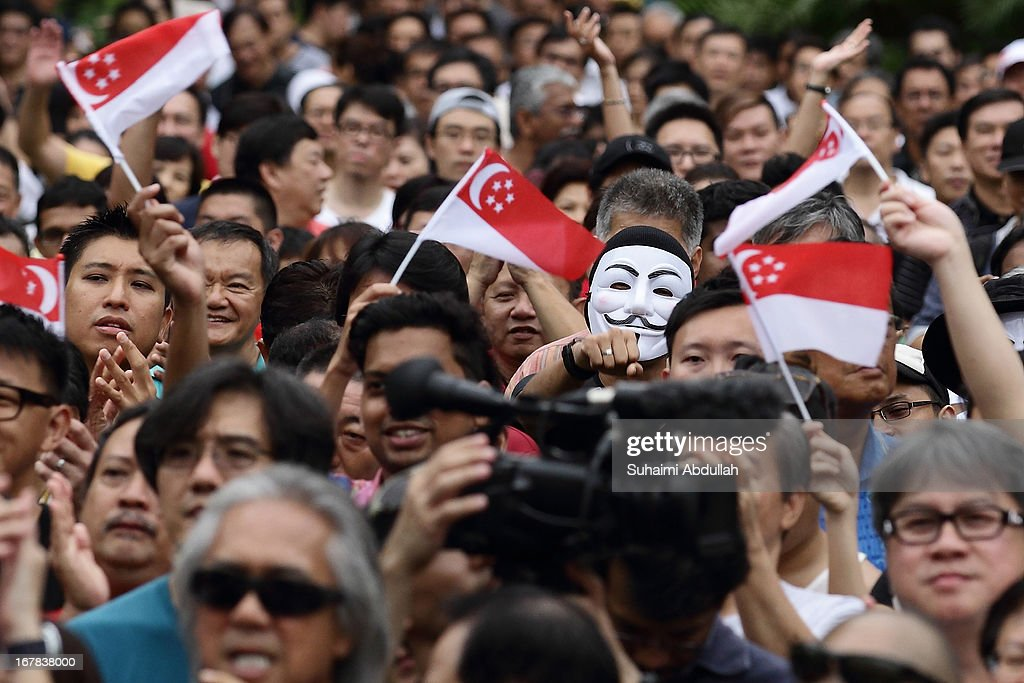 People react to a speaker during the protest against the government's White Paper on Population and labour-related matters that affect Singaporeans at Speakers' Corner in Hong Lim Park on May 1, 2013 in Singapore. Thousands of protesters gathered today in an inaugural labour day protest against the 6.9 million population government white paper that revealed it could increase 30% to 6.9 million by 2030, angering residents who already see a strain on housing, transportation and healthcare. This is a follow up protest after one was held on 16 Feb, 2013 organised by the same organiser, transitioning.org
