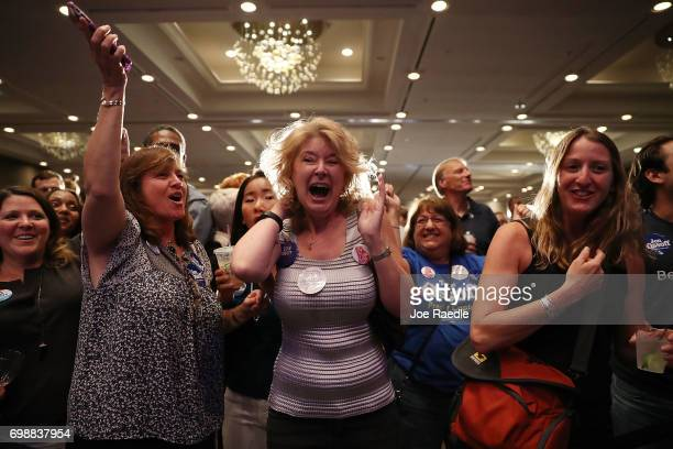 People react to election results that show their candidate Democratic candidate Jon Ossoff up against his challenger at an election night party being...