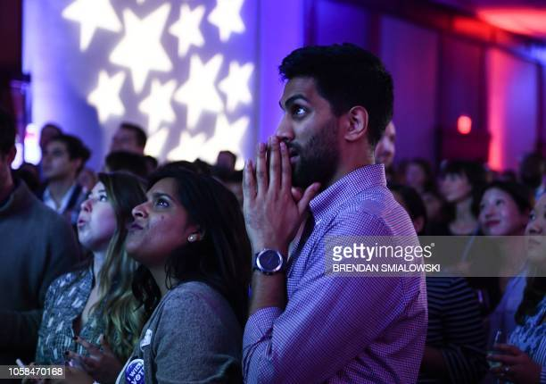 TOPSHOT People react to live results while attending a midterm election night party hosted by the Democratic Congressional Campaign Committee...