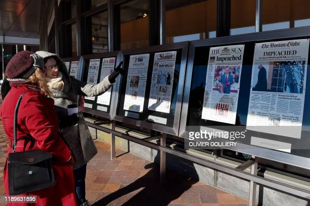 People react to newspaper front pages on display at the Newseum in Washington DC on December 19 after US President Donald Trump's historic...