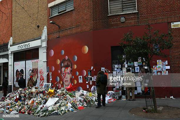 People read and pay their respects near the flowers letters and other items left on a mound continue to grow two weeks after the death of Brixton...