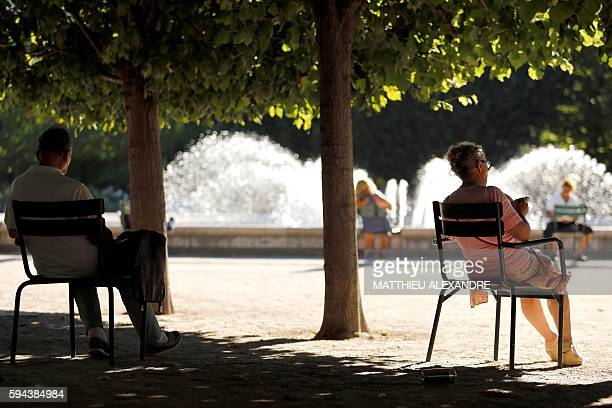 People read as they sit on chairs in front of a fountain at the Jardin du Palais Royal in Paris on August 23 2016 / AFP / MATTHIEU ALEXANDRE