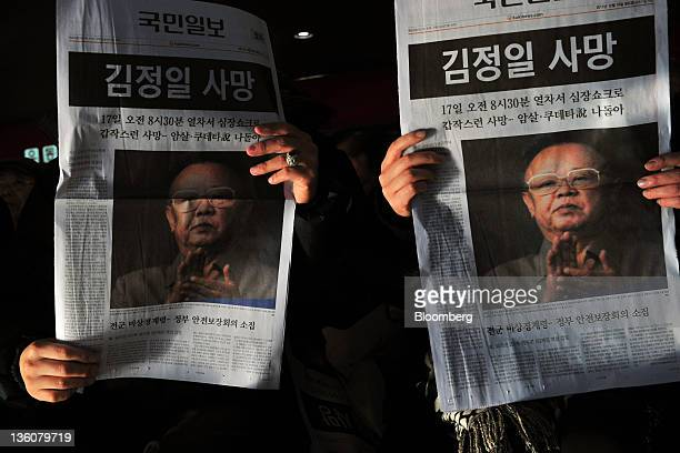 People read copies of an extra edition newspaper reporting the death of Kim Jong Il leader of North Korea at Seoul Station in Seoul South Korea on...