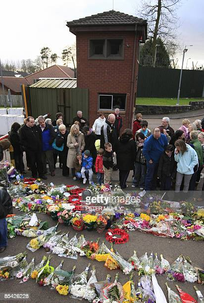 People read floral tributes during a prayer vigil at the front of the Massereen Army base in Co. Antrim, Northern Ireland on March 14, 2009 after two...