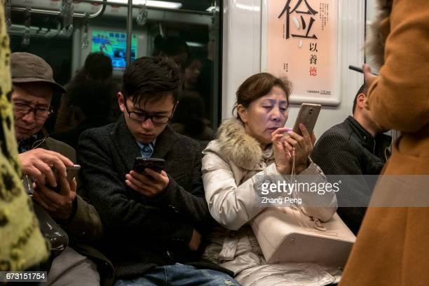 People read on smart phone in subway train. In China, the sales of smart phone have accounted for 96% of total mobile phone market, while smart phone...