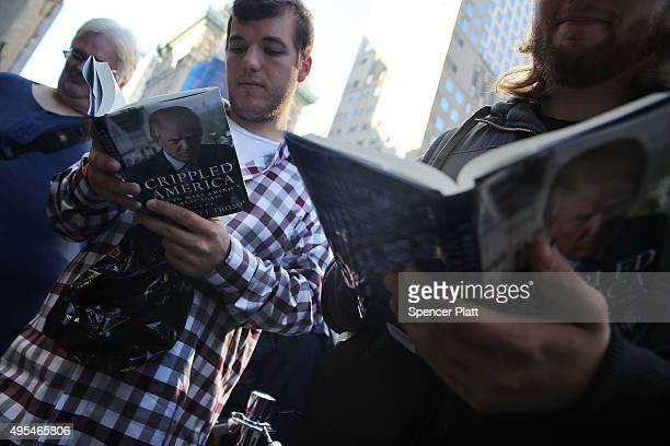 People read Republican presidential candidate Donald Trump's new book 'Crippled America How to Make America Great Again' while waiting in line at a...