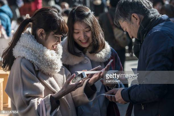 People read their 'omikuji' fortunetelling paper strips after praying for the new year at Tsurugaoka Hachimangu Shinto shrine on January 1 2018 in...