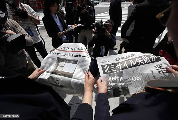 People reading copies of an extraedition newspaper reporting the launch of a North Korean rocket are surrounded by the media in Tokyo Japan on Friday...