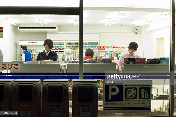 People reading magazines at convenience store