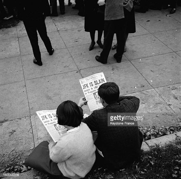 People reading newspaper in Lafayette Park after the assassination of President John Fitzgerald Kennedy on November 23 1963 in Washington DC United...