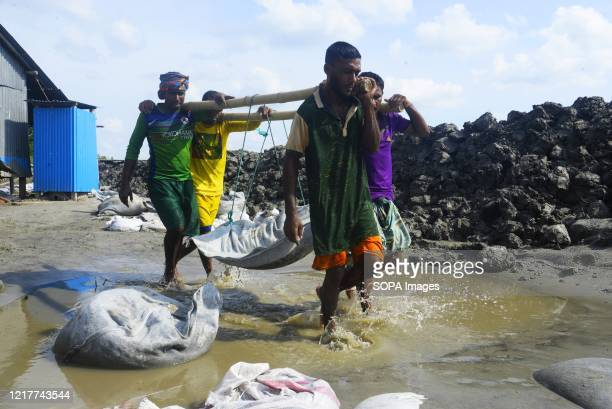 People rebuild their dam during the aftermath of an extremely severe cyclonic storm Amphan. Thousands of shrimp enclosures have been washed away,...