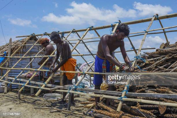 People rebuild their house in the aftermath of the extremely severe cyclonic storm Amphan. Thousands of shrimp enclosures have been washed away,...