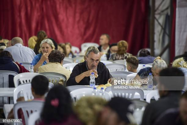 People receive a free Iftar meal as they break their fast during the last day of the Muslim holy month of Ramadan on June 14 2018 in the Kosovo...